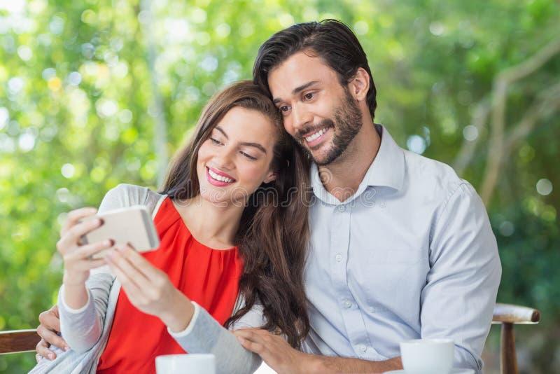 Uśmiechnięta para bierze selfie podczas gdy siedzący obraz royalty free