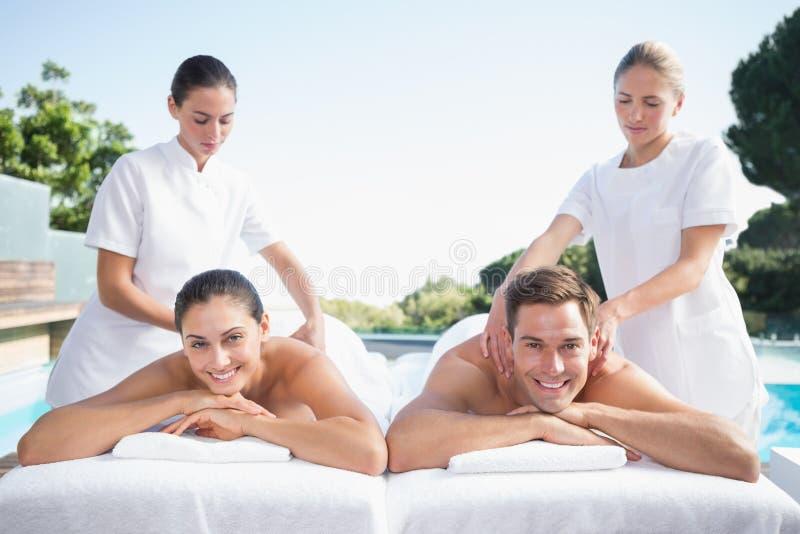 Uśmiechnięta para cieszy się para masażu poolside fotografia stock