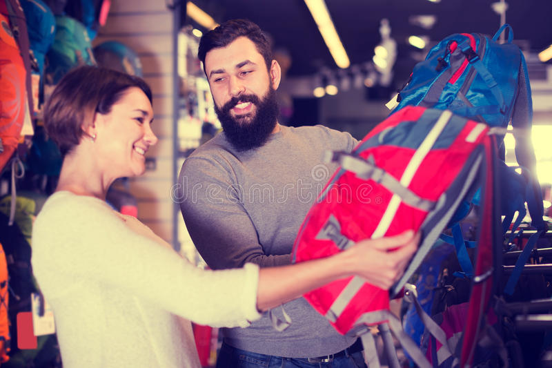 Uśmiechnięta para egzamininuje plecaki w sporta wyposażenia sklepie zdjęcia stock