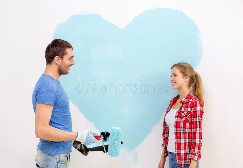 Uśmiechnięta para maluje dużego serce na ścianie obrazy stock