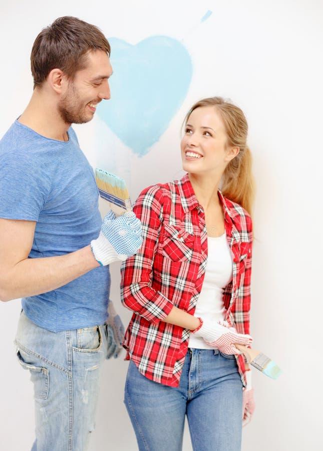 Uśmiechnięta para maluje małego serce na ścianie obrazy royalty free