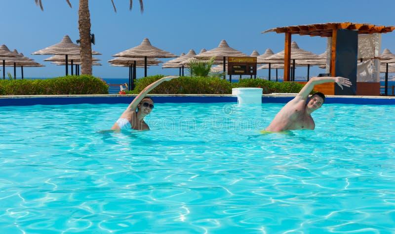 Uśmiechnięta para robi aqua sprawności fizycznej w pływackim basenie zdjęcia stock