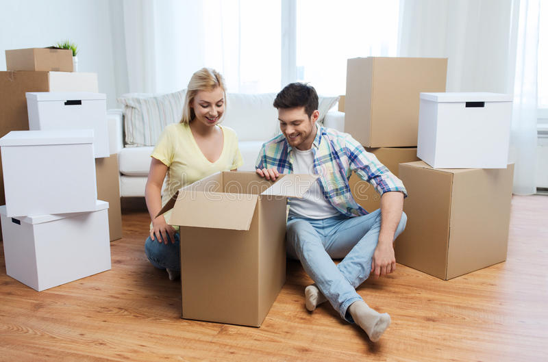 Uśmiechnięta para rusza się nowy dom z dużymi pudełkami zdjęcie stock