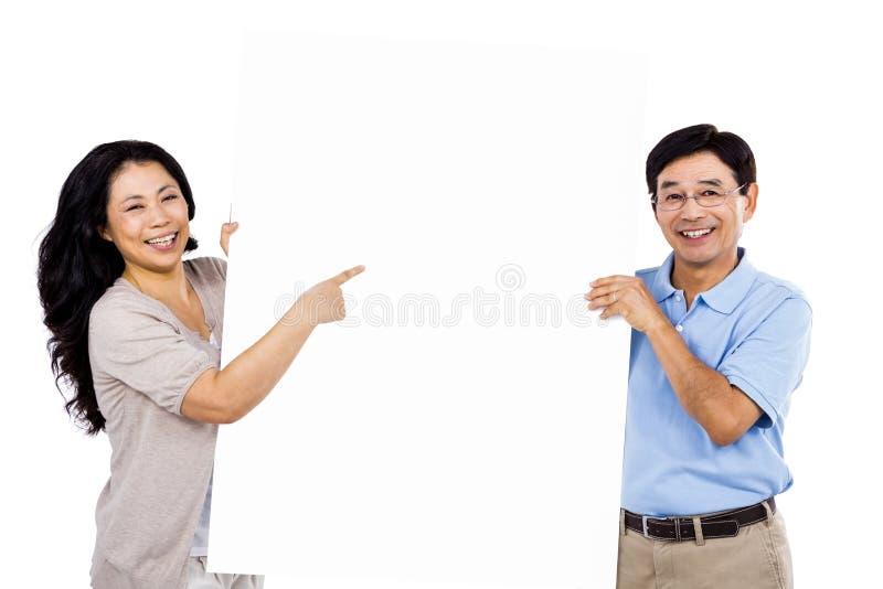 Uśmiechnięta para trzyma up wielkiego znaka zdjęcie royalty free