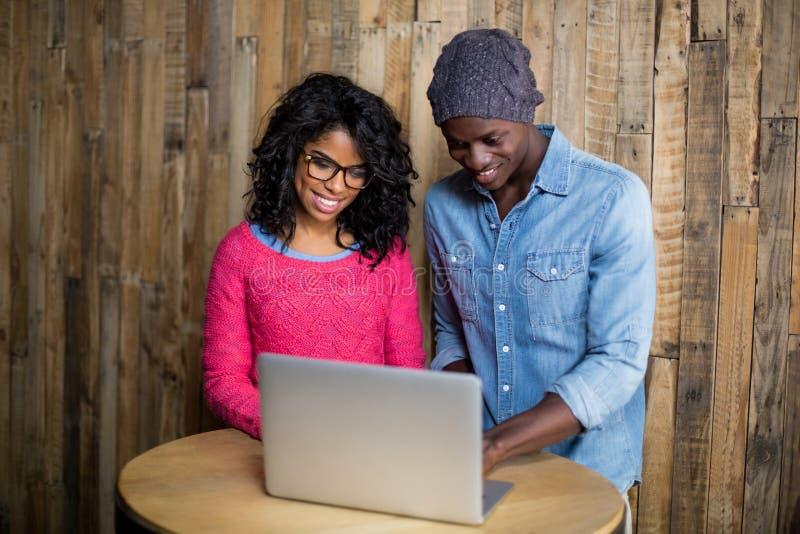 Uśmiechnięta para używa laptop zdjęcie stock