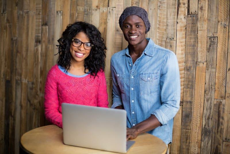 Uśmiechnięta para używa laptop w café obraz stock