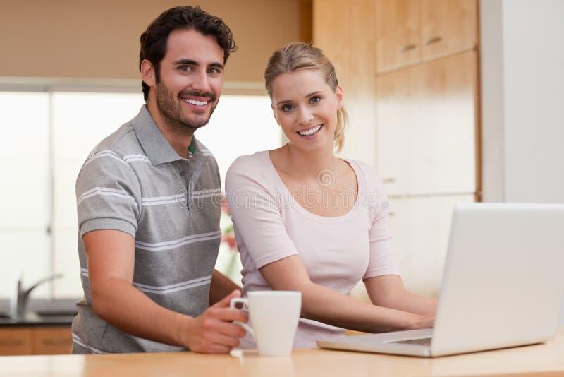 Uśmiechnięta para używa notatnika podczas gdy mieć kawę obrazy stock