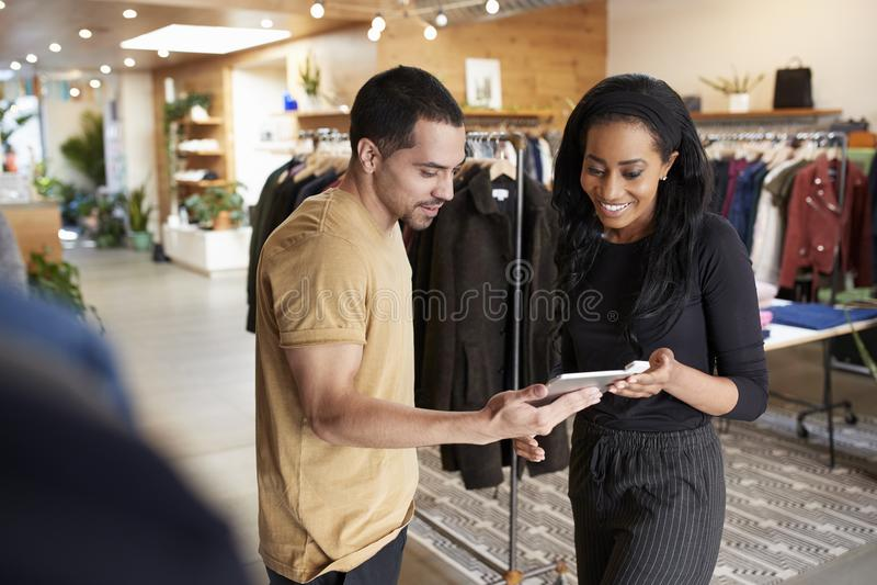 Uśmiechnięta para używa pastylka komputer w odzieżowym sklepie zdjęcia royalty free