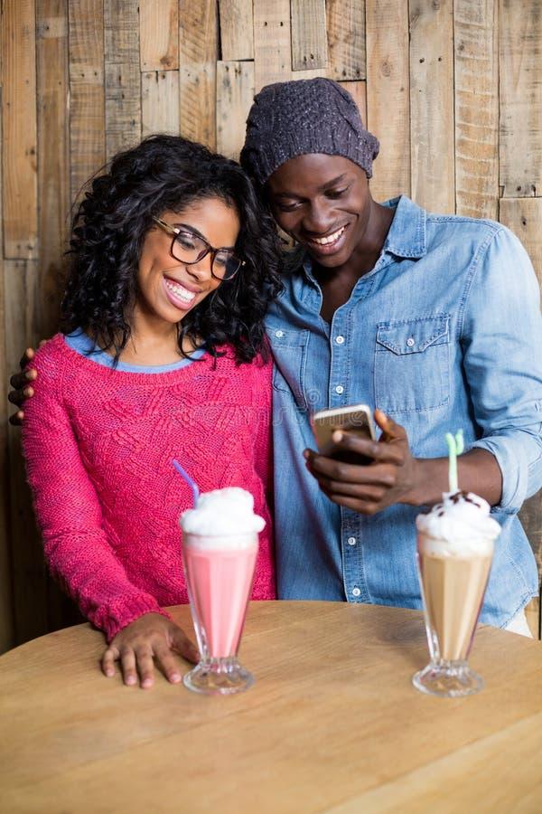 Uśmiechnięta para używa telefon komórkowego przeciw drewnianemu tłu fotografia stock