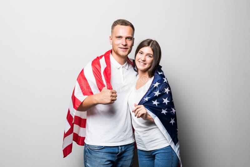 Uśmiechnięta para w miłości pozuje z usa flagą odizolowywającą na szarym tle Szczęśliwa przystojna chłopiec w białej koszula i ła fotografia royalty free