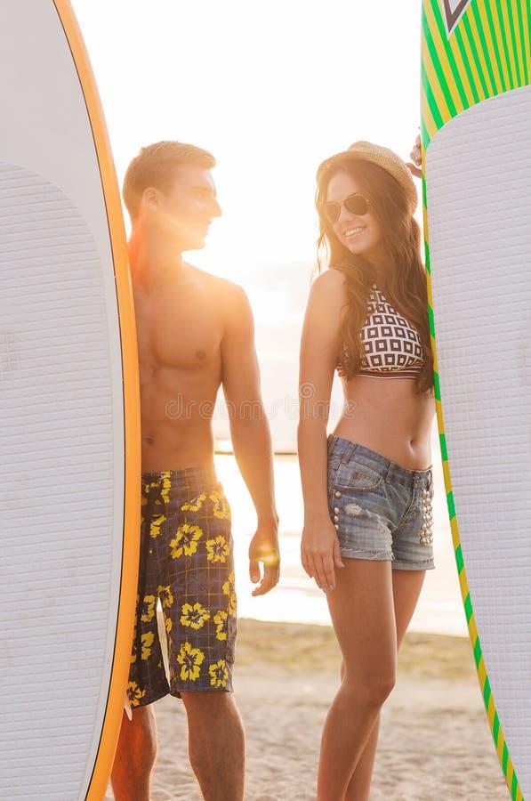 Uśmiechnięta para w okularach przeciwsłonecznych z surfuje na plaży obraz royalty free