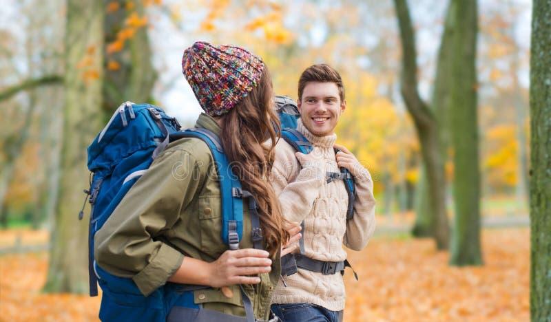 Uśmiechnięta para wycieczkuje w jesieni z plecakami zdjęcie royalty free