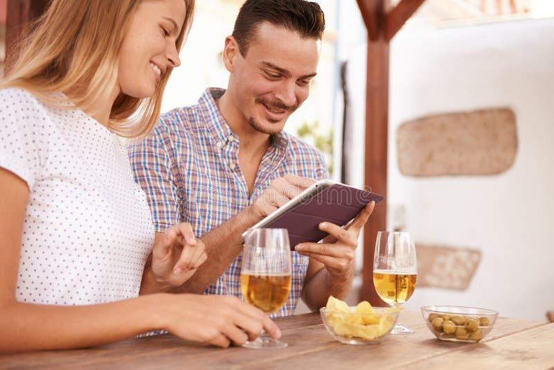 Uśmiechnięta para z piwami i touchpad obraz stock