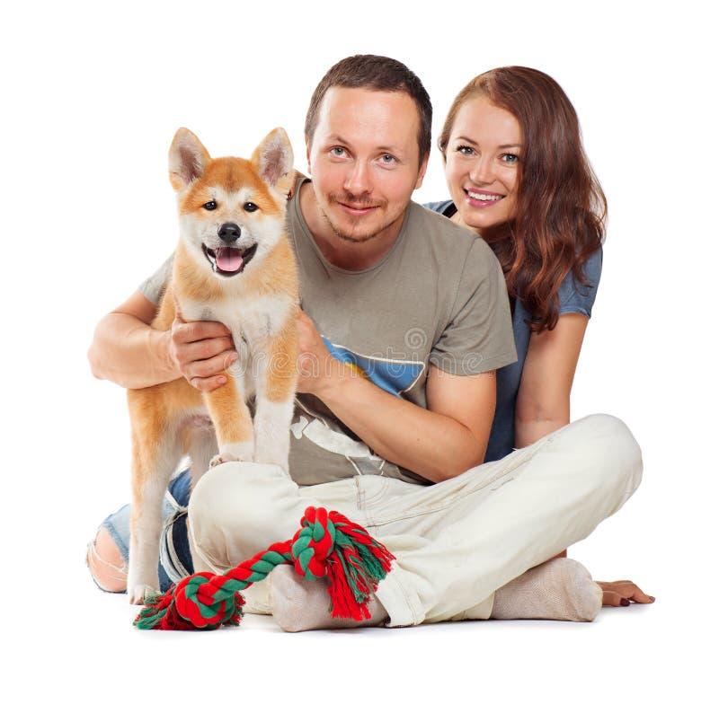 Uśmiechnięta para z psim obsiadaniem wpólnie zdjęcia royalty free