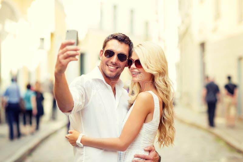 Uśmiechnięta para z smartphone w mieście zdjęcia royalty free