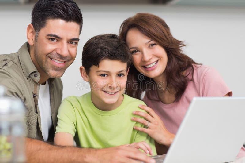 Uśmiechnięta para z synem używa laptop obrazy stock