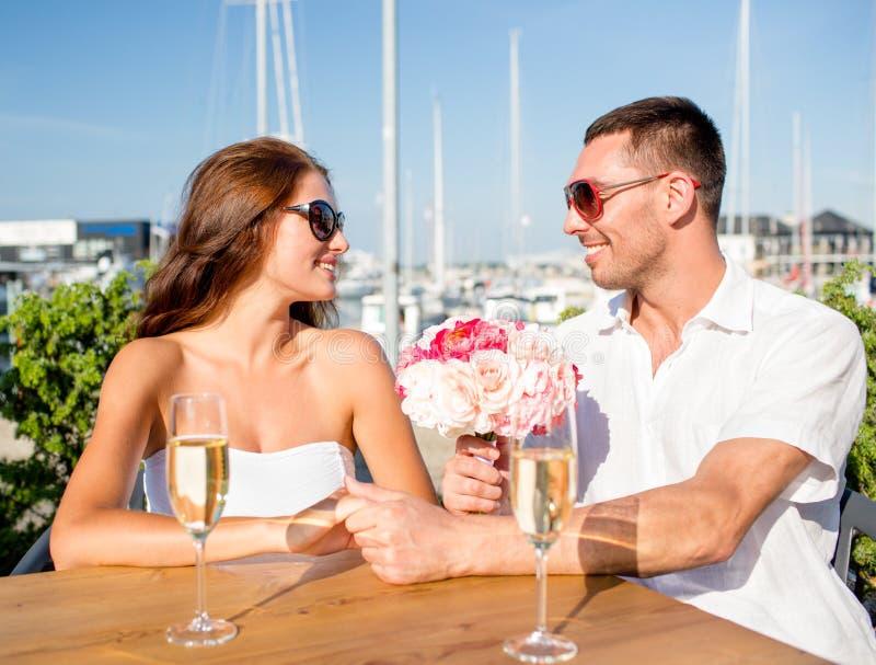 Uśmiechnięta para z wiązką i szampan przy kawiarnią zdjęcie stock
