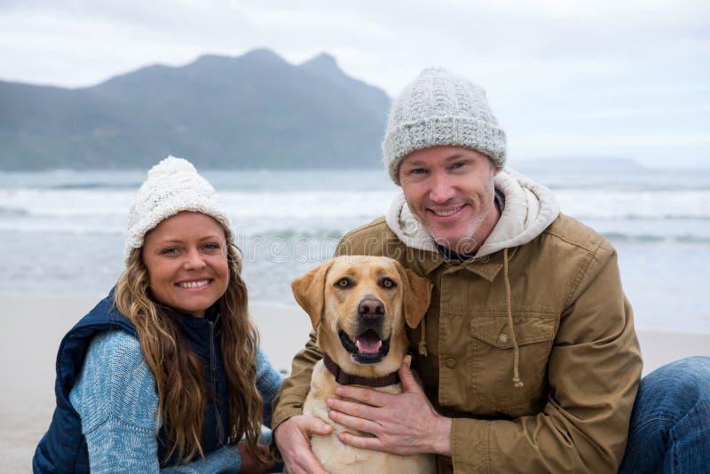 Uśmiechnięta para z zwierzę domowe psem przy plażą zdjęcie royalty free