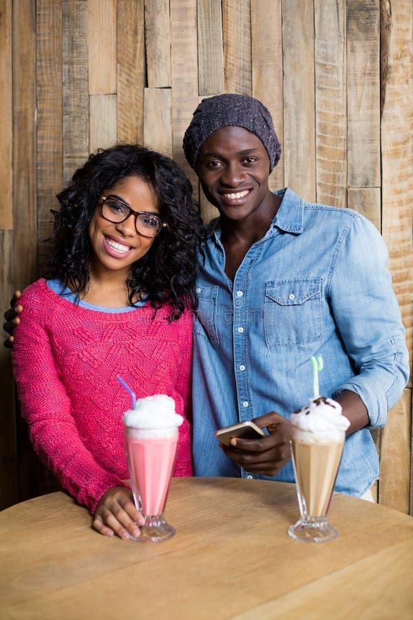 Uśmiechnięta pary pozycja przeciw drewnianemu tłu w café zdjęcie stock