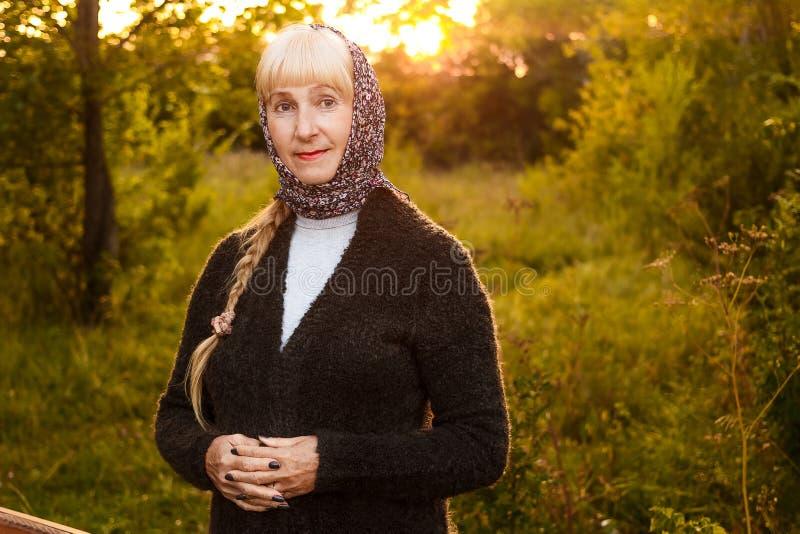 Uśmiechnięta pięćdziesięcioletnia kobieta patrzeje kamerę w lecie przy zmierzchem w szaliku na jej kardiganie i głowie zdjęcie royalty free