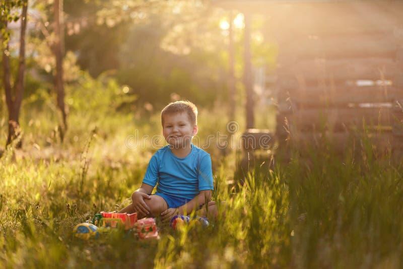 Uśmiechnięta pięcioletnia chłopiec w błękitów ubraniach bawić się z samochodami w lata obsiadaniu na trawie w świetle obrazy royalty free