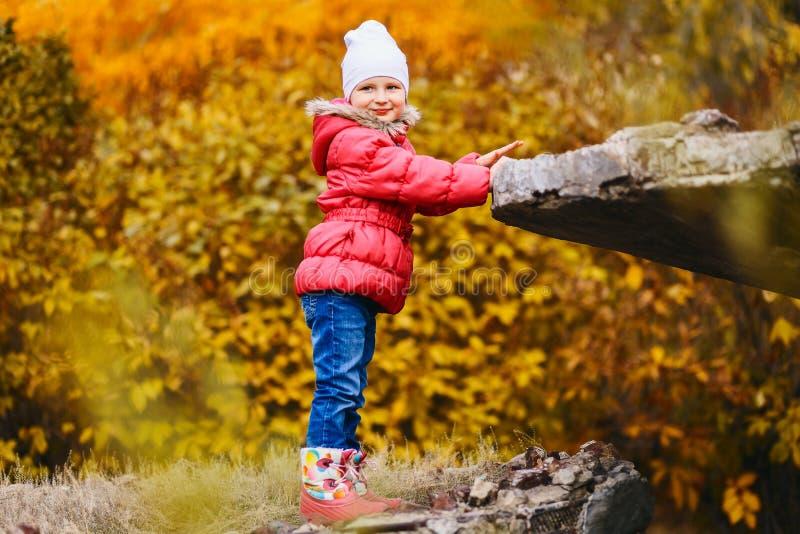 Uśmiechnięta pięcioletnia stara dziewczyna w kurtce na jesień kolorze żółtym opuszcza tło obraz stock
