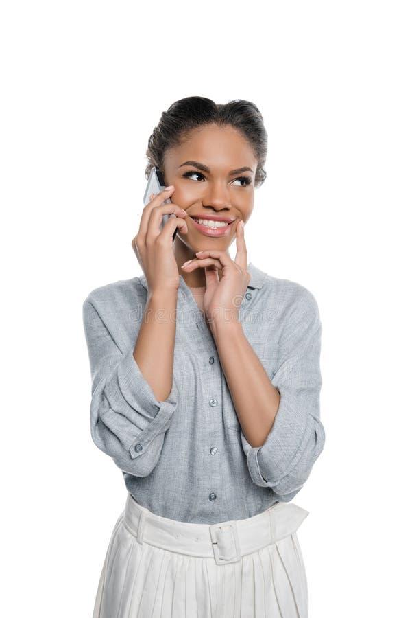 Uśmiechnięta piękna amerykanin afrykańskiego pochodzenia dziewczyna opowiada na smartphone i patrzeje daleko od fotografia stock