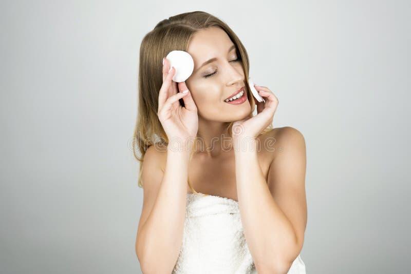 Uśmiechnięta piękna blond kobieta w biały ręcznikowy jeden mienia bawełnianym ochraniaczu blisko jej czoła i innym bawełnianym oc zdjęcia royalty free