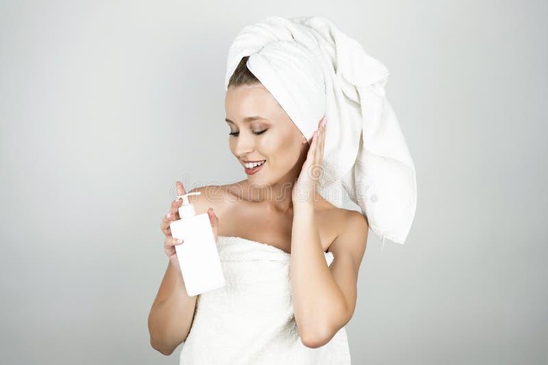 Uśmiechnięta piękna blond kobieta w białym ręczniku nad ciałem na jej kierowniczej mienia ciała śmietance i odizolowywał białego  obraz stock
