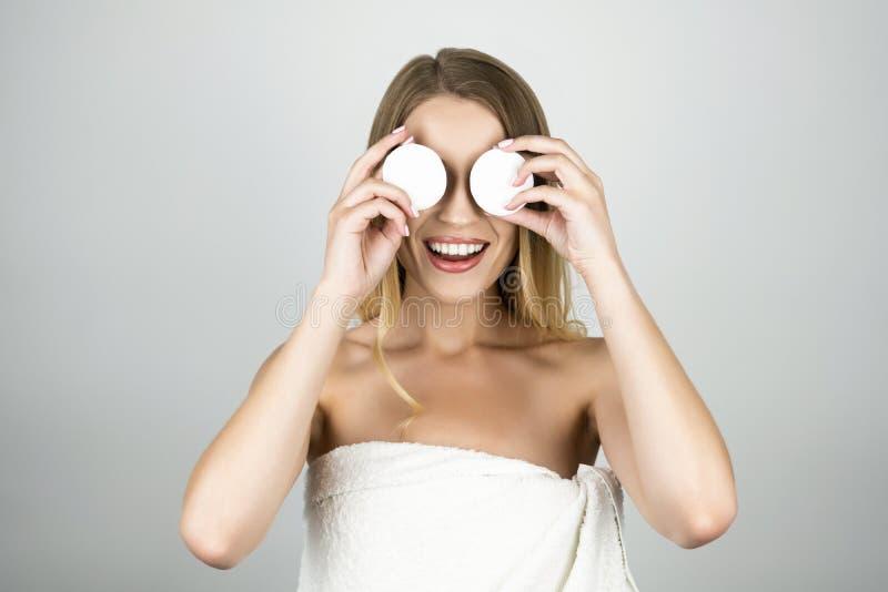 Uśmiechnięta piękna blond kobieta w białym ręczniku stosuje bawełnianych ochraniaczów na jej oczach odizolowywał białego tło fotografia royalty free