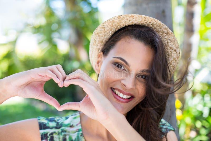 Uśmiechnięta piękna brunetka robi kierowemu kształtowi z ona ręki obrazy royalty free