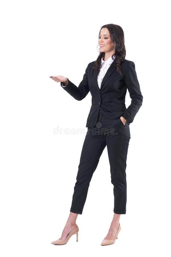 Uśmiechnięta piękna elegancka biznesowa kobieta w formalnym odziewa pokazywać pustą przestrzeń z otwartą palmą obraz stock