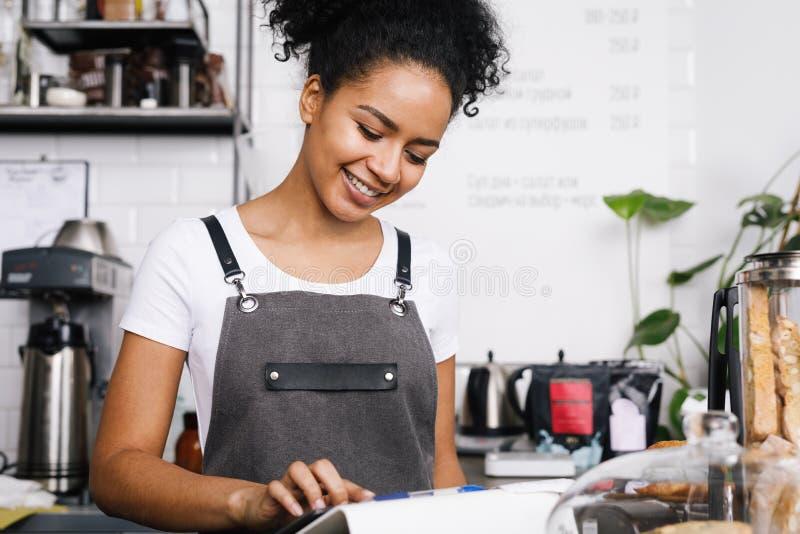 Uśmiechnięta piękna kelnerka używa cyfrową pastylkę zdjęcie stock
