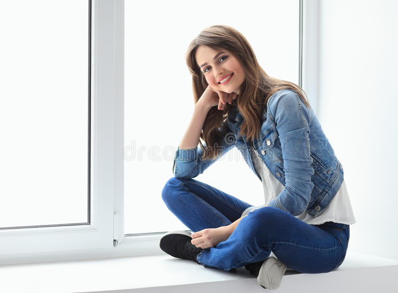 Uśmiechnięta piękna kobieta relaksuje na nadokiennym parapecie fotografia stock