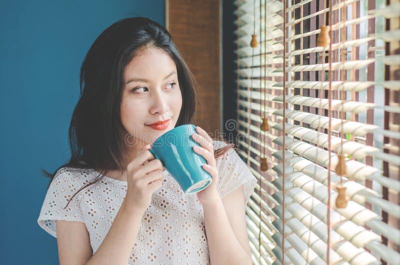 Uśmiechnięta piękna kobieta stoi blisko okno i trzyma dobry kawowy salowego w rankach zawsze robi ja w dobrym nastroju fotografia royalty free