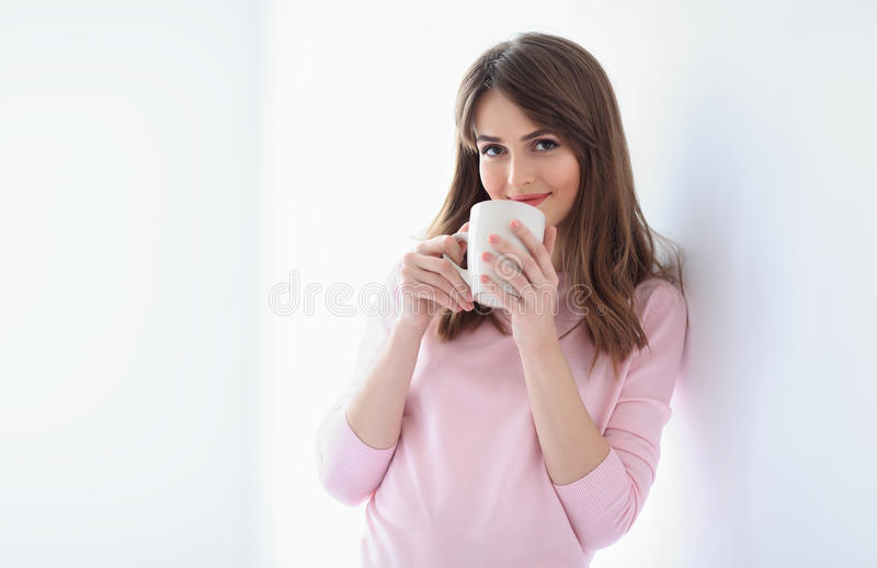 Uśmiechnięta piękna kobieta z filiżanką kawy na białym tle zdjęcia stock