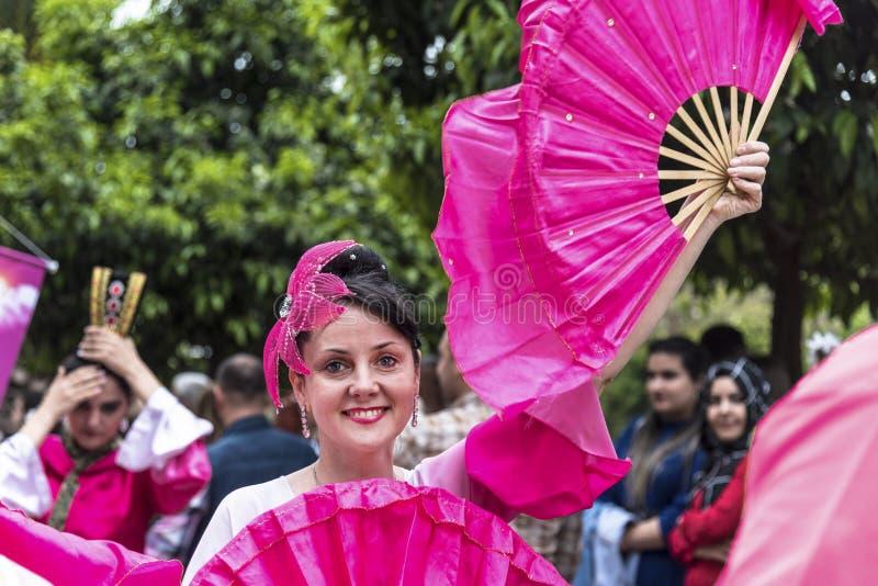 Uśmiechnięta piękna kobieta z ręki fan pinky menchia kostiumem w Pomarańczowym okwitnięcie Karnawałowej parady otwarciu i Adana,  fotografia stock
