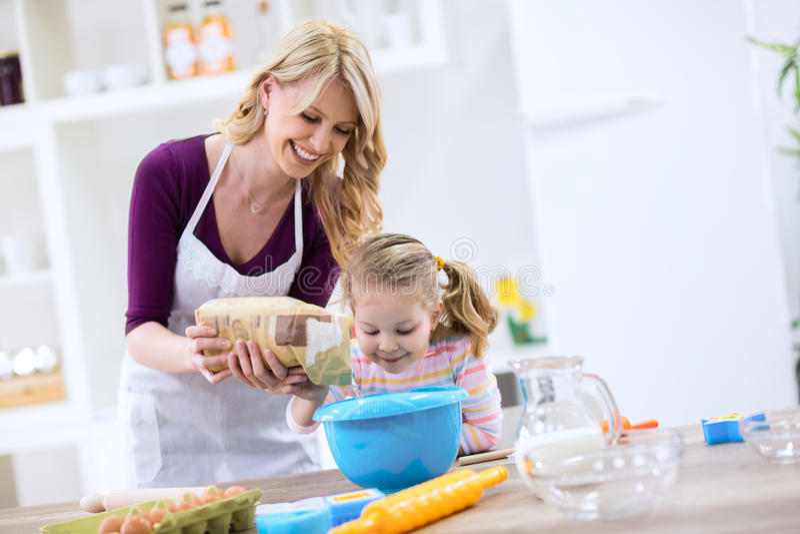 Uśmiechnięta piękna mama z dziecka kładzenia mąką fotografia royalty free