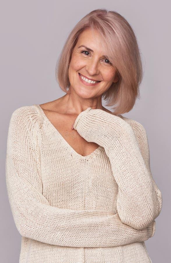 Uśmiechnięta piękna w połowie starzejąca się kobieta odizolowywająca obrazy royalty free