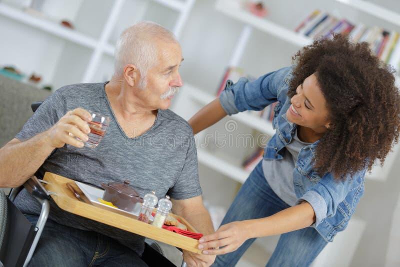Uśmiechnięta pielęgniarka daje jedzeniu starszy mężczyzna w domu zdjęcie royalty free