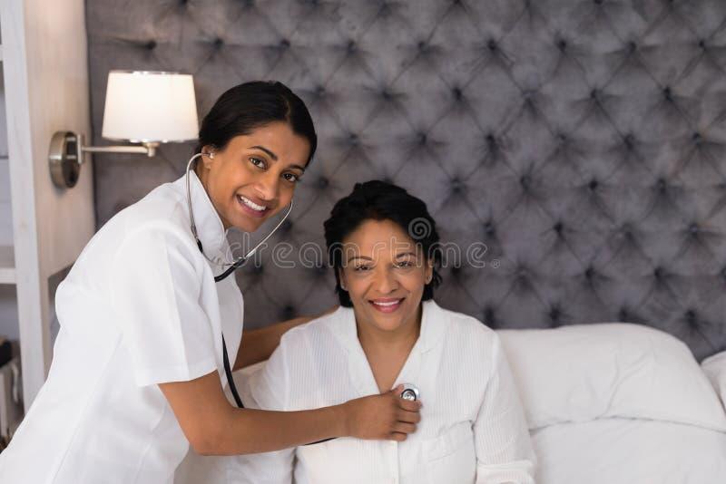 Uśmiechnięta pielęgniarka egzamininuje dojrzałej kobiety odpoczywa na łóżku w domu obraz royalty free