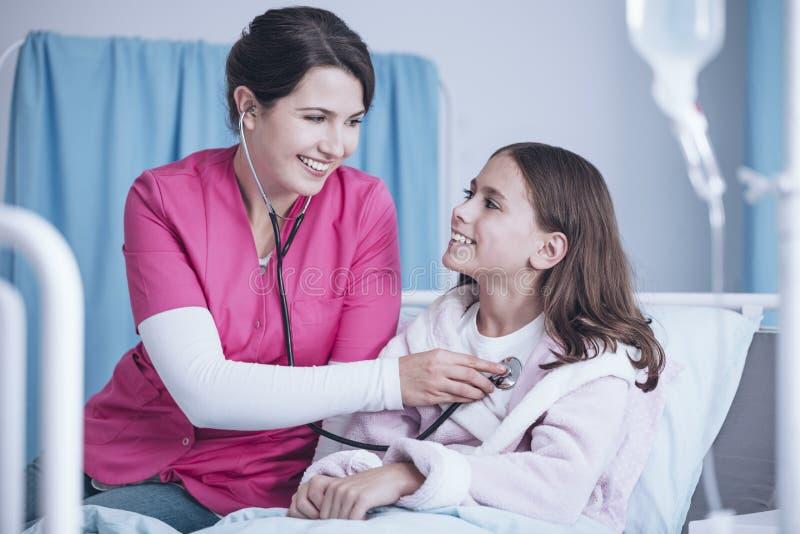 Uśmiechnięta pielęgniarka egzamininuje szczęśliwej dziewczyny w hospi z stetoskopem fotografia royalty free