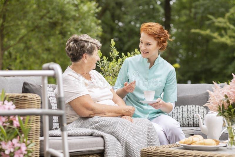 Uśmiechnięta pielęgniarka opowiada szczęśliwa starsza kobieta podczas spotkania dalej zdjęcie royalty free
