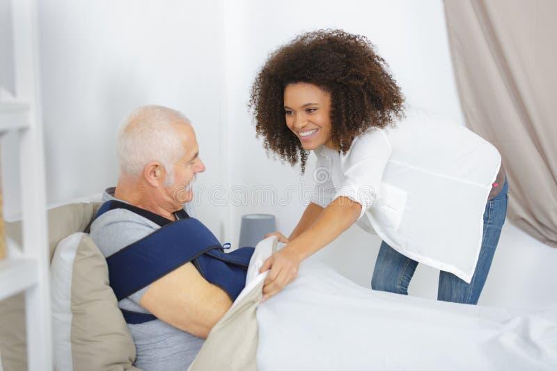 Uśmiechnięta pielęgniarka pociesza starszego mężczyzna zdjęcia stock
