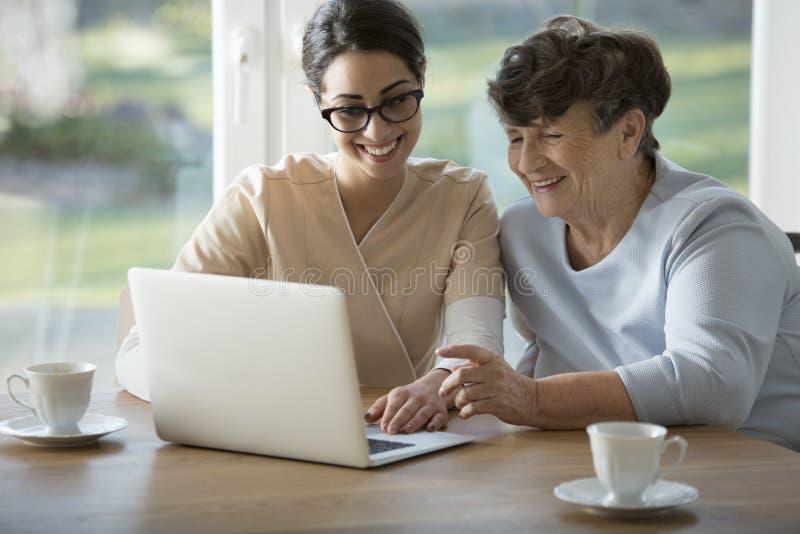 Uśmiechnięta pomocnicza nauczanie starszych osob kobieta zdjęcie stock