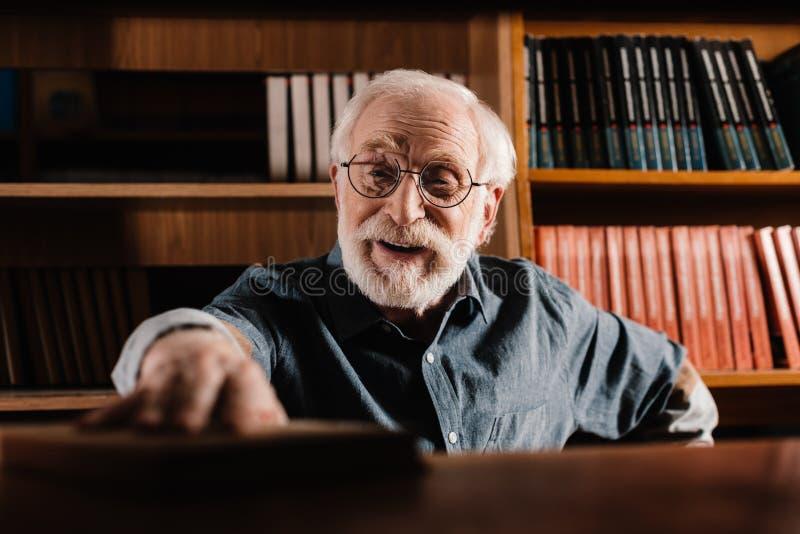 uśmiechnięta popielata włosiana bibliotekarska bierze książka od obraz stock