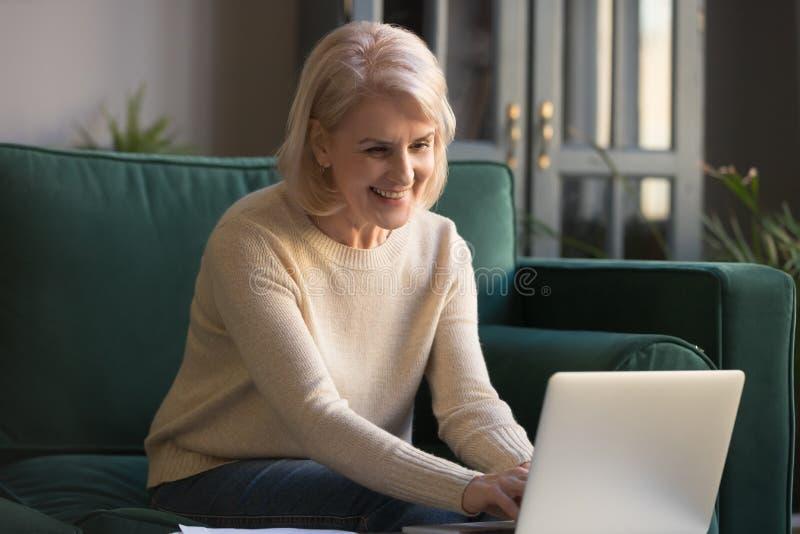 Uśmiechnięta popielata z włosami zadowolona dojrzała kobieta używa laptop w domu zdjęcia royalty free