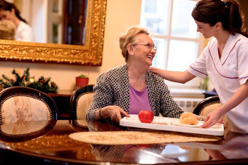 Uśmiechnięta potomstwo pielęgniarka przynosi śniadanie starsza kobieta przy pielęgnacją obraz stock