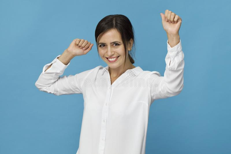 Uśmiechnięta pozytywna kobieta z atrakcyjnym spojrzeniem, będący ubranym białą koszulkę, pozuje przeciw błękitnej pustej ścianie obraz stock