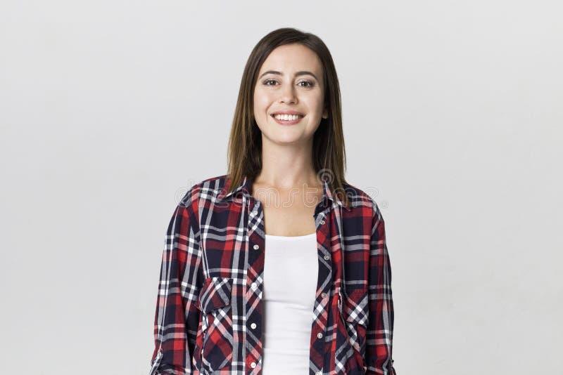 Uśmiechnięta pozytywna kobieta z atrakcyjnym spojrzeniem, będący ubranym w kratkę koszula, pozuje przeciw białej pustej ścianie obraz stock